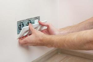 de handen van een elektricien die een stopcontact installeert foto