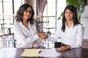 twee glimlachende zakelijke vrouwen handen schudden en zitten aan tafel
