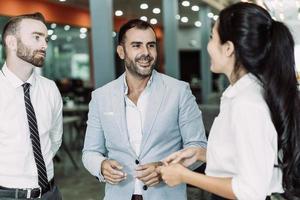 drie positieve mensen uit het bedrijfsleven chatten in de lobby van het kantoor foto