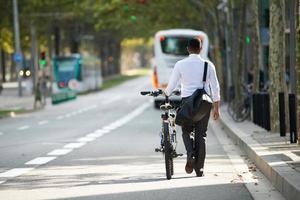 zakenman wandelen met fiets in straat na het werk foto