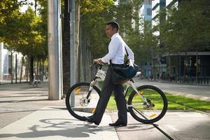 Spaanse kantoormedewerker met fiets oversteken straat foto