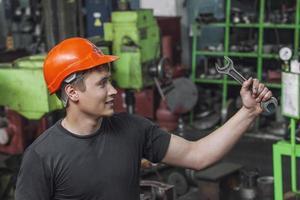 de jonge man die in de oude fabriek aan de installatie werkt foto