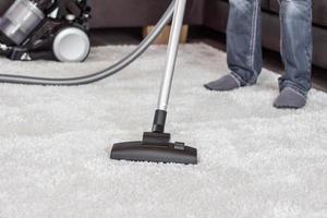 man maakt het tapijt schoon met een stofzuiger