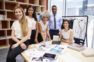 creatief team dat aan camera in een bureau glimlacht foto