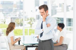 doordachte zakenman met collega's in vergadering achter foto