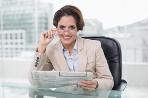 Glimlachende zakenvrouw krant houden op haar bureau foto