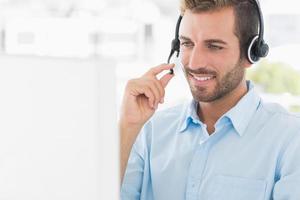 casual jonge man met hoofdtelefoon met behulp van computer foto