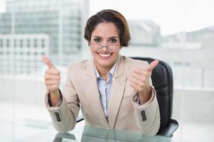 gelukkig zakenvrouw duimen opdagen op haar bureau foto