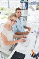 glimlachend toevallig jong paar dat aan computers werkt foto