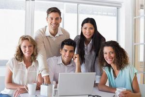 casual glimlachend commercieel team dat een vergadering heeft die laptop met behulp van foto