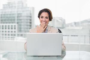 verrast zakenvrouw met behulp van laptop op haar bureau foto