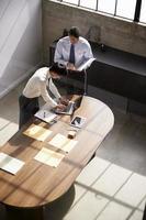 twee zakenlieden staan te werken aan een bureau in een kantoor foto