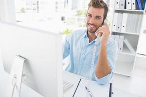 glimlachende mens die telefoon en computer in bureau met behulp van foto