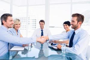 leidinggevenden handen schudden tijdens zakelijke bijeenkomst foto