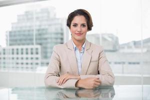 ontspannen zakenvrouw camera kijken op haar bureau foto