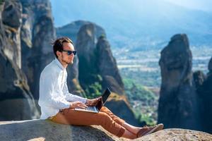 man met laptop op de bergen foto