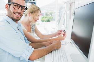 glimlachend toevallig jong paar dat aan computer werkt foto