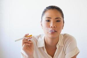 casual zakenvrouw roken van een elektronische sigaret foto