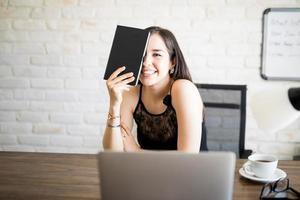 vrolijke jonge vrouw achter haar bureau foto