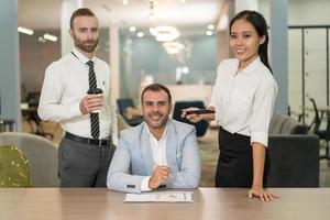 mensen uit het bedrijfsleven werken en poseren aan balie in kantoor foto