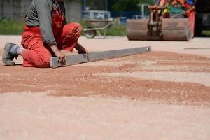werknemer op een bouwplaats probeert het oppervlak te egaliseren foto
