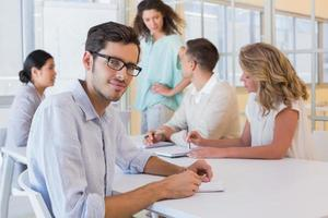 casual zakenman lachend op camera tijdens vergadering foto