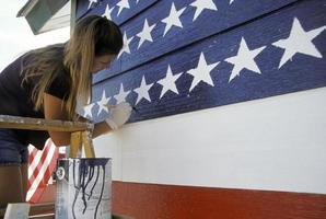 jonge vrouw die de vlag van de VS op de muur schildert foto