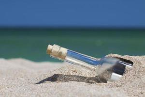 bericht in een fles met zee en de horizon foto