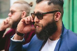 bebaarde zakenman kijken naar telefoon foto