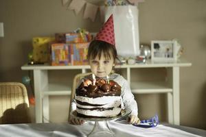 klein meisje staat op het punt verjaardagskaarsen te blazen foto