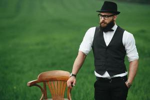 man met een baard, denken in het veld in de buurt van stoel