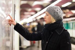 dame die op het paneel van de kaart van het openbaar vervoer kijkt.