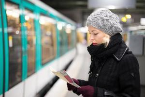 dame te wachten op metrostation platform.