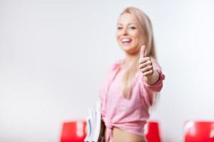glimlachende student met haar duim omhoog en glimlachend foto