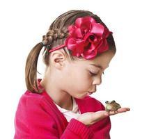 kleine prinses die een kikker kust foto