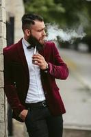 rijke man met een baard rookt elektronische sigaret foto