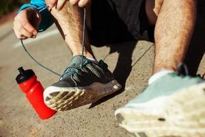 sportman stropdas schoenveters op zijn loopschoenen in het park foto