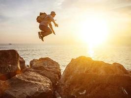 dappere man springen bij zonsondergang foto