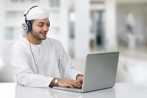 jonge Arabische zakenman die aan zijn notitieboekje werkt foto