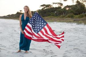 vrouw houdt Amerikaanse vlag terwijl je op het strand foto