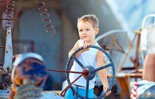 schattige kindjongen doet alsof ze een denkbeeldige auto bestuurt foto