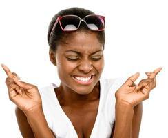 schattige Afro-Amerikaanse vrouw vingers gekruist geïsoleerd op wit foto