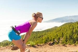 jonge vrouw haalt adem in de bergen foto