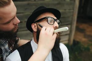Kapper scheert een bebaarde man foto