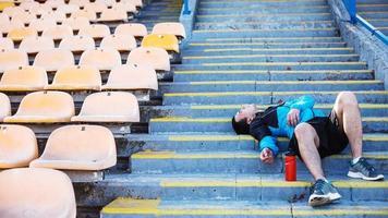 moe sportman liggend op de trap in het stadion foto