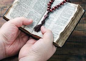 houten rozenkrans en een christelijk kruis in zijn hand
