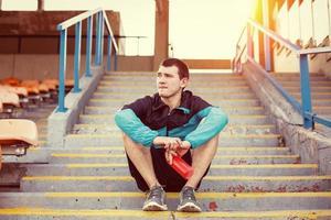 sportman die bij het stadion rust foto