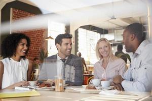 ondernemers ontmoeten in coffeeshop schot door raam foto