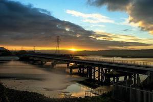 Britse trein over een brug bij zonsondergang foto