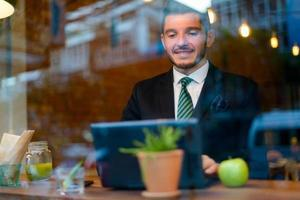zakenman met behulp van laptopcomputer in coffeeshop foto